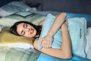 Frau, die im Bett liegt und Kissen umarmt