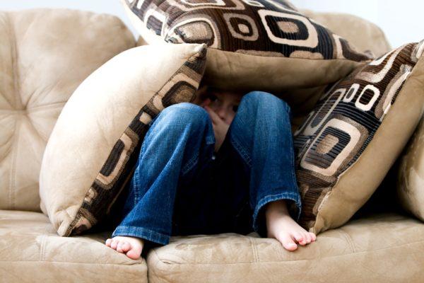 Kind versteckt sich hinter Kissen